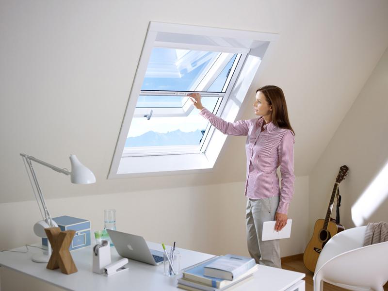Frau öffnet ein Dachfenster mit Insektenschutz