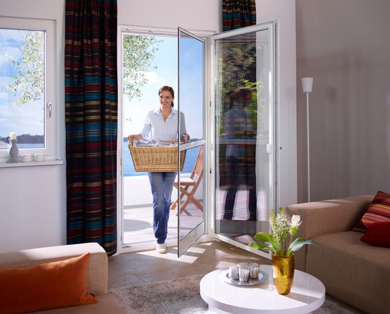 Frau betritt Wohnung durch eine Drehtür mit Insektenschutz