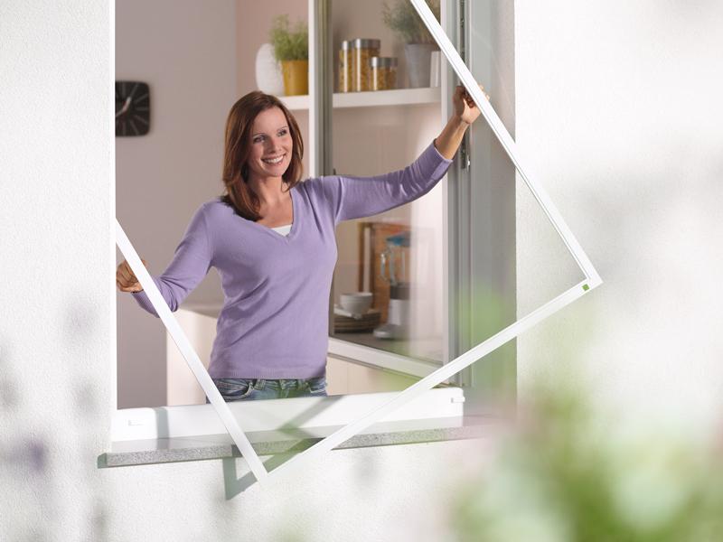 Frau bringt Fensterrahmen mit Insektentschutz an